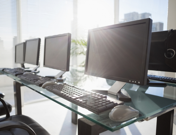 Computers on desk in front of a window office