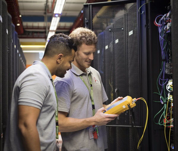 Two men checking the the connection of wires