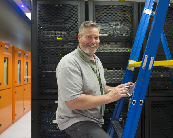 Man working inside a server room leaning at the ladder