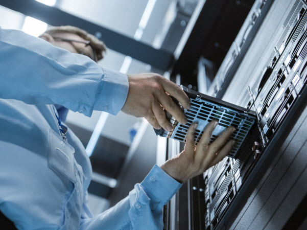 Man inside a room of centre cable servers